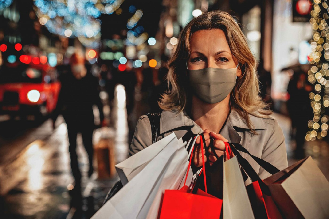 Portrait of a woman wearing a facemask while Christmas shopping and holding bags – COVID-19 pandemic lifestyle concepts